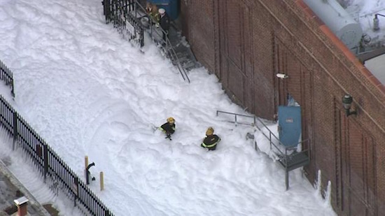 Firefighters enveloped in foam after a fire suppression system released at a Philadelphia substation.