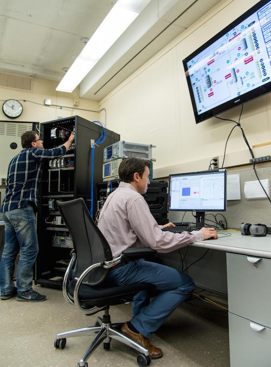 Rick Candell (seated) and Murat Aksu (standing) examine how wireless communications perform in a virtual chemical processing plant created by the NIST Industrial Wireless Test Bed.